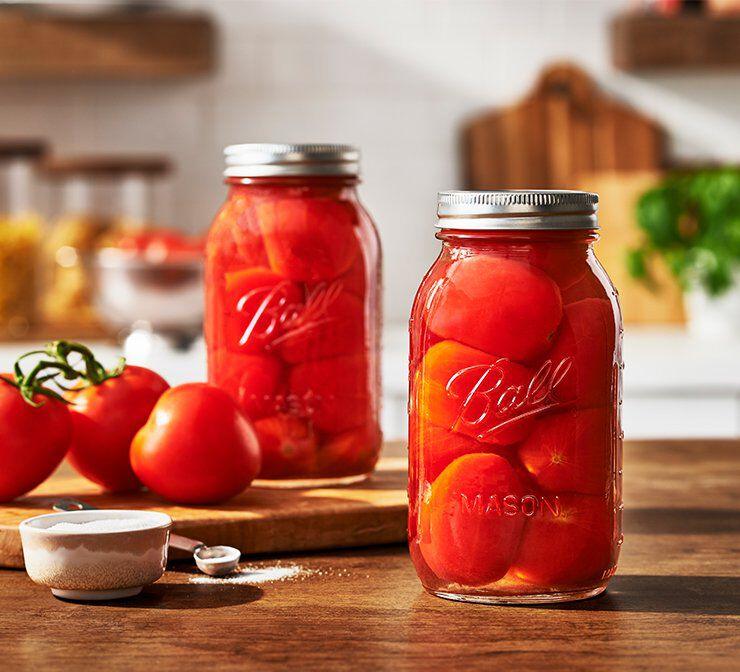 Glass canning jars with lids and bands preserving tomatoes